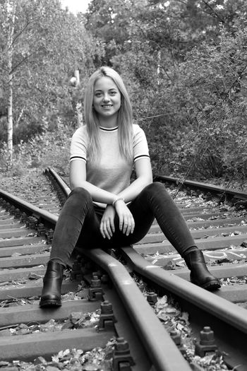 Portrait of young woman sitting on railroad track