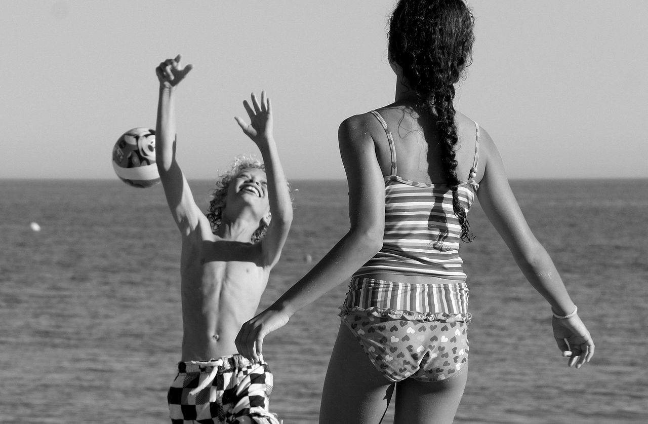 real people, leisure activity, sea, arms raised, beach, lifestyles, outdoors, day, standing, horizon over water, casual clothing, water, togetherness, young women, sky, sunlight, nature, young adult, clear sky, friendship