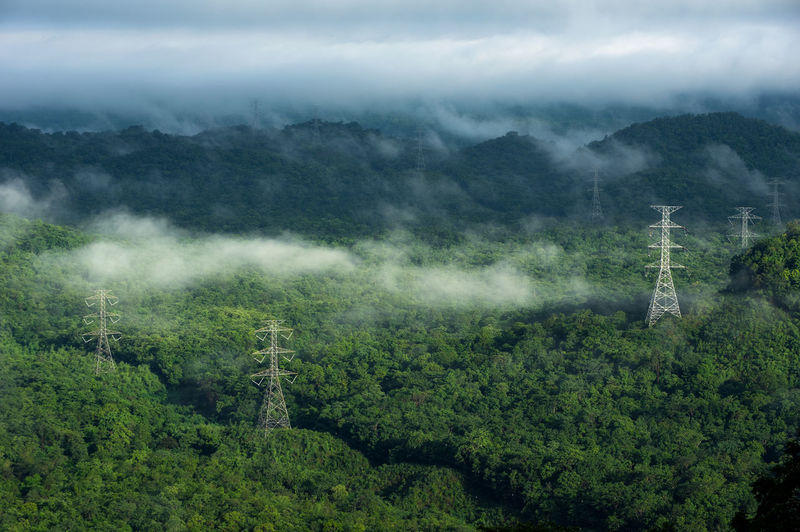 High voltage power transmission towers in fog on mountain mae moh lampang.