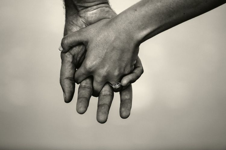Close-Up Of Cropped Holding Hands Against White Background