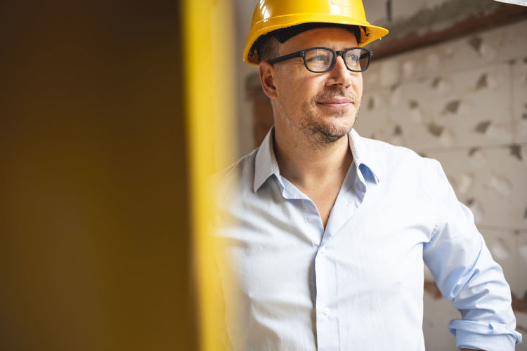 Man working against yellow wall