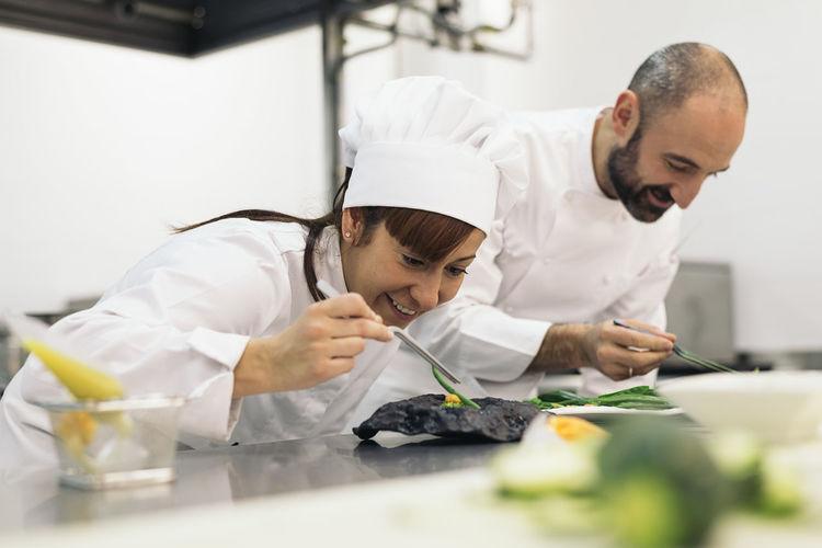 Chefs garnishing food on kitchen in restaurant
