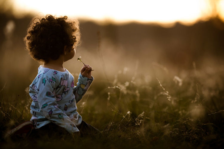 Girl sitting on field during sunset