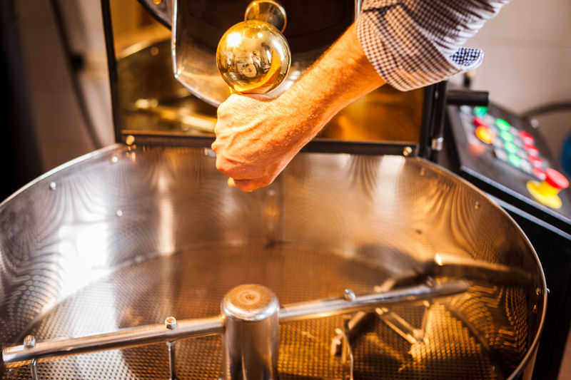 Cropped hand of barista preparing coffee in machinery at cafe