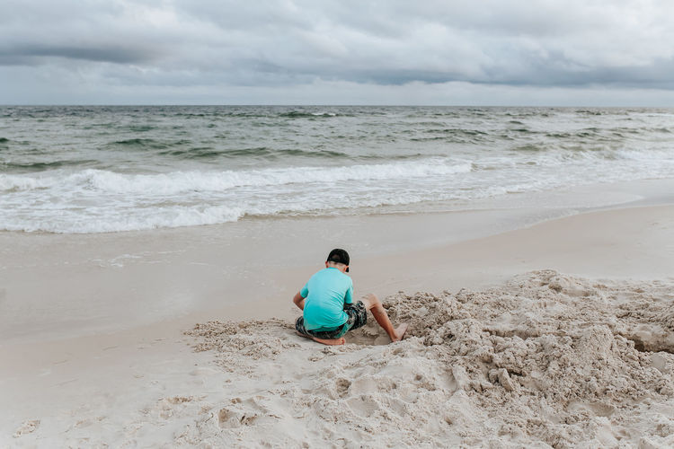 Rear view of man sitting on shore at beach against sky
