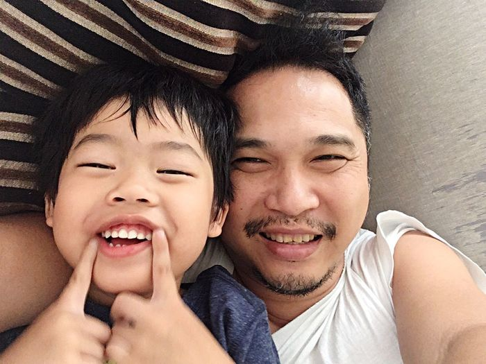 Portrait of father and son smiling while lying on bed