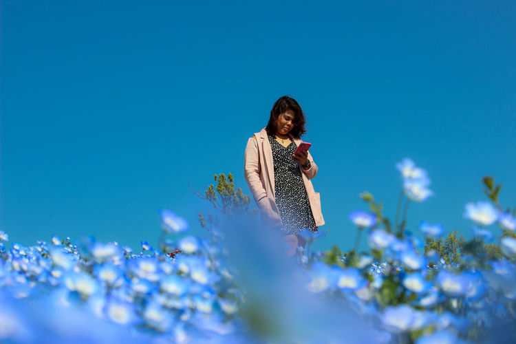 Young woman on flowering plants against blue sky