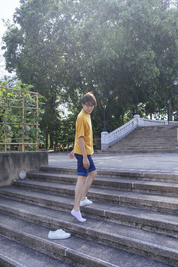Full length young man standing on steps at park