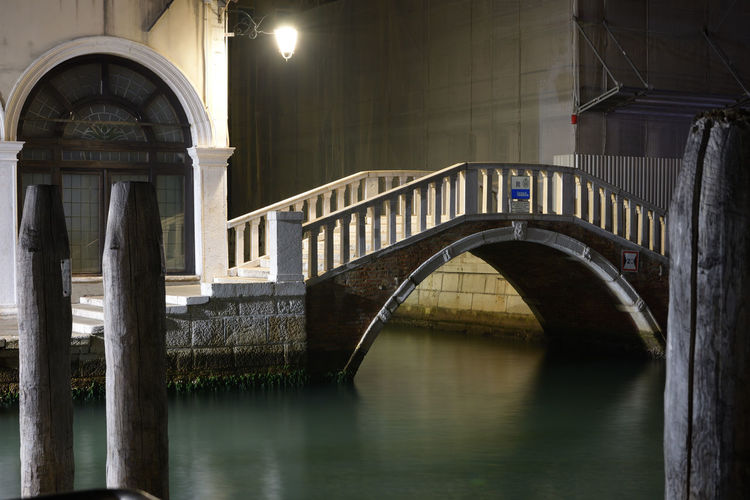 Arch bridge over river at night