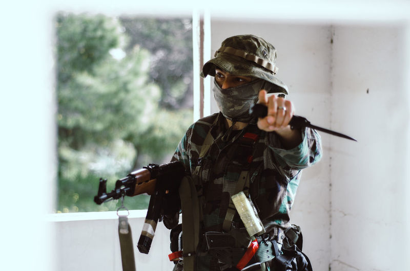 Special forces soldier holding rifle gun point finger at you looking at camera One Person Government Camouflage Clothing Army Soldier Armed Forces Military Uniform Clothing Military Uniform Army Young Adult Waist Up Weapon Gun Day Rifle Real People Sport Standing Machine Gun Special Forces Aggression
