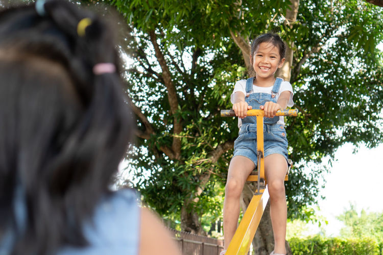 Low angle view of friends playing on seesaw at playground