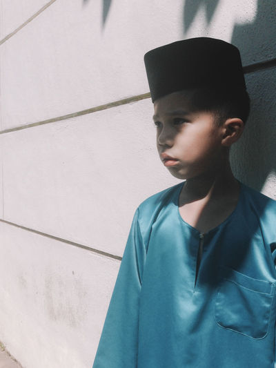 Boy Wearing Traditional Cap By Wall