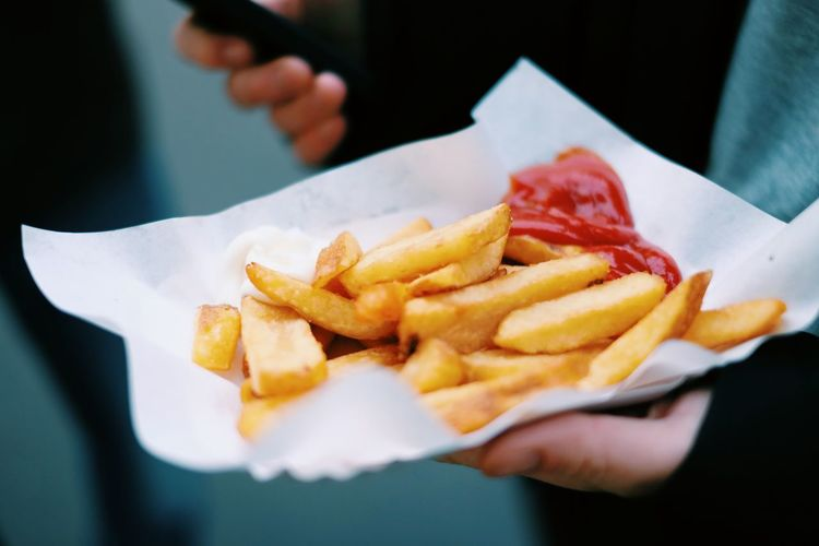 Cropped Image Of Hand Holding French Fries With Ketchup
