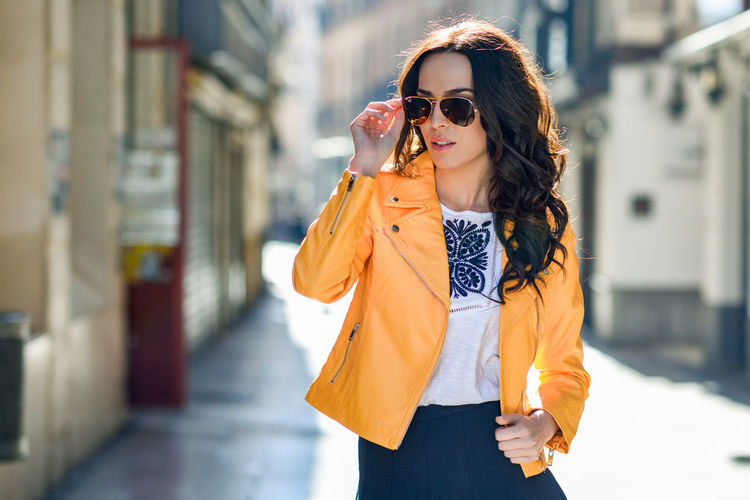 Young brunette woman with sunglasses. Girl, model of fashion, wearing orange modern jacket and blue skirt, standing in urban background. Aviator Sunglasses Architecture Beautiful Woman Beauty Casual Clothing City Clothing Fashion Focus On Foreground Front View Glasses Hair Hairstyle Leisure Activity Lifestyles One Person Outdoors Real People Standing Sunglasses Three Quarter Length Young Adult Young Women