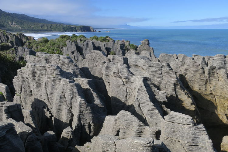 Panoramic view of rocks and sea against sky