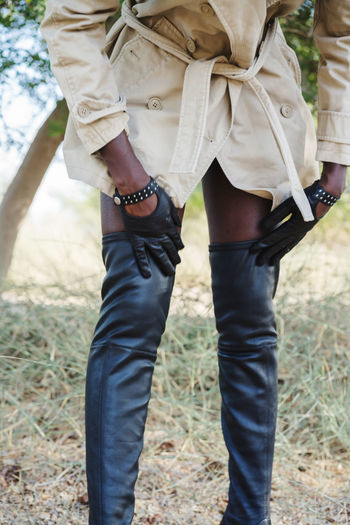 Black woman wearing trench coat and over the knee high boots