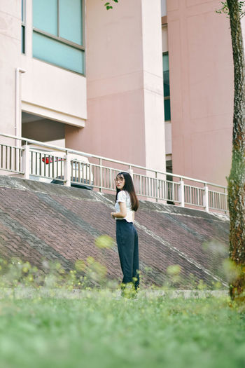 Portrait of young woman standing on grass in front of building at park