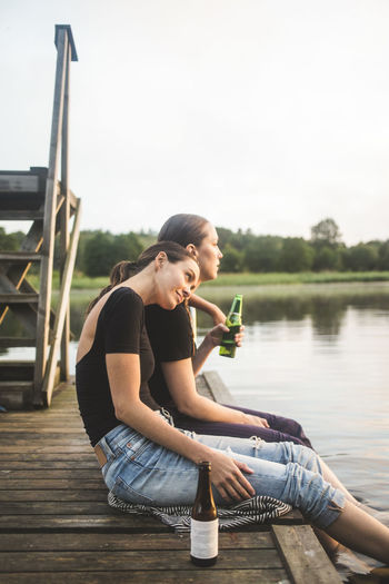 Woman sitting by lake against clear sky