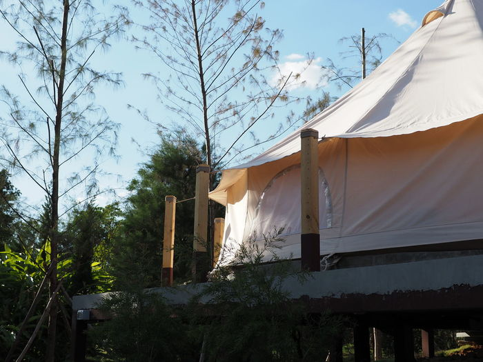 Low angle view of tent by building against sky