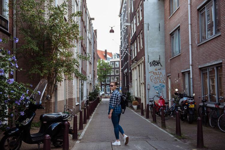 Man walking on street amidst buildings in city
