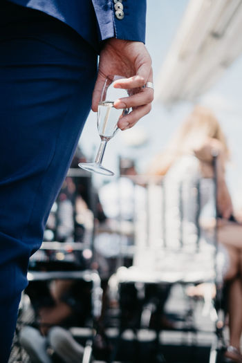 Midsection Of Woman Holding Champagne Flute While Standing Outdoors