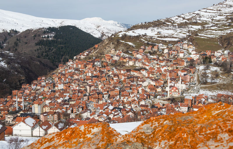Aerial view of townscape by snow covered mountain