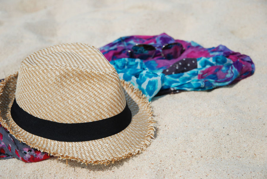 cdb8124d640c67 Beach summer accessories on sandy tropical beach. Straw hat, sunglasses and  colorfull scarf on