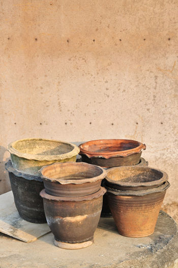 High angle view of clay pots on table by wall