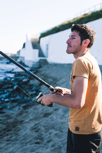 Side view of young man standing against sea