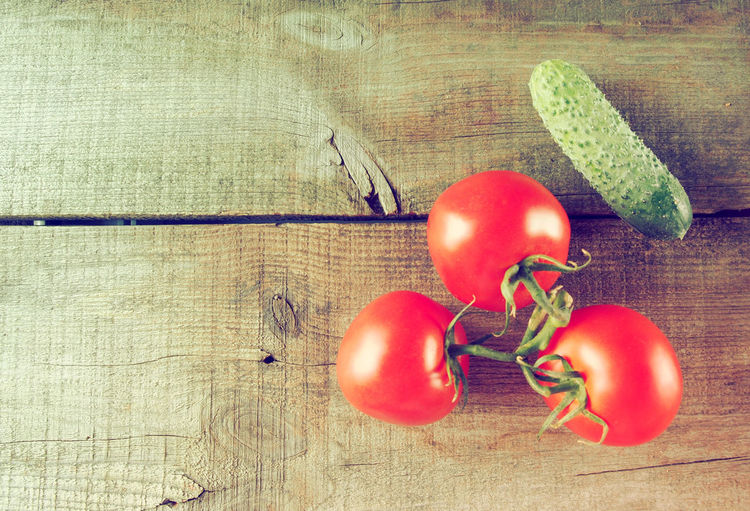 Directly Above Shot Of Tomatoes And Cucumber On Wooden Table