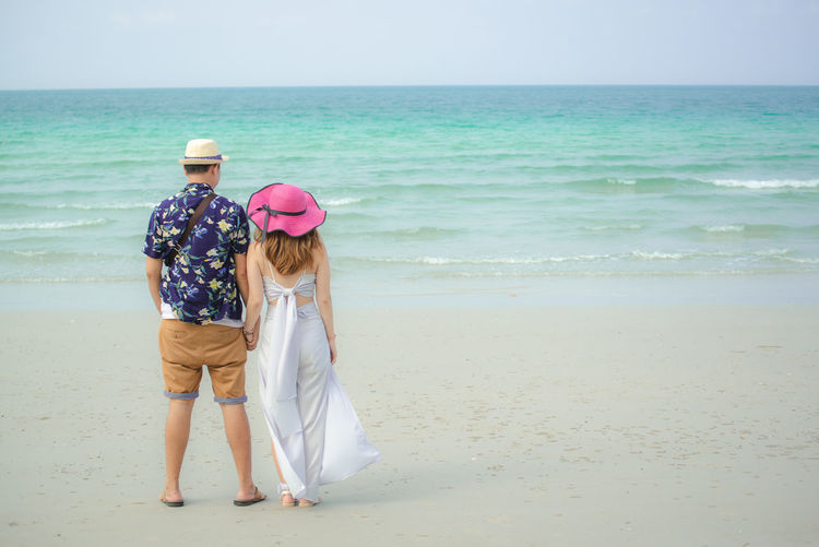 Sea Beach Land Water Two People Full Length Rear View Leisure Activity Togetherness Horizon Over Water Sky Casual Clothing Horizon Scenics - Nature Hat Standing Sand Bonding Women Nature Positive Emotion Couple - Relationship Arm Around Couple Wedding