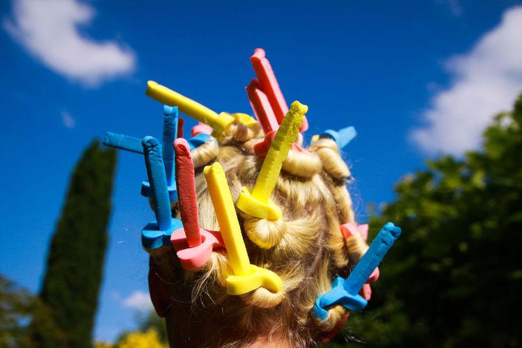 Woman wearing hair curlers against blue sky