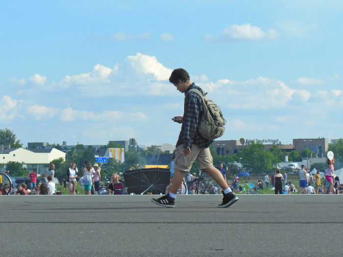 Walking down one of the two runways of the former Berlijn airport Tempelhof is considerred as a kind of meditation. On the picture a boy on his way while checking his mobile phone. Berlin Tempelhofer Feld City Outdoors People Phone Real People Walking