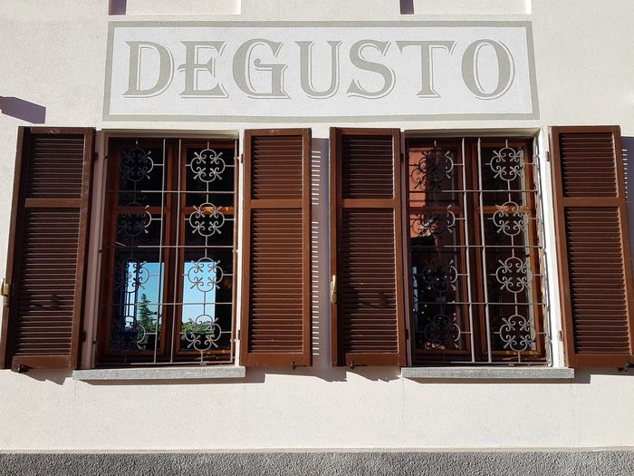 Windows and wall script Degusto Wall Building Exterior Indoor Outdoor Details Background Windows Pair Wall Script Architecture Close-up Metal Grate Western Script Pattern Text Capital Letter Written