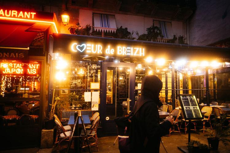 Man and illuminated restaurant in city at night