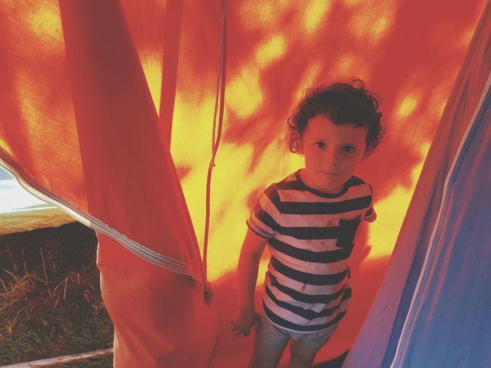 Portrait of boy standing in tent