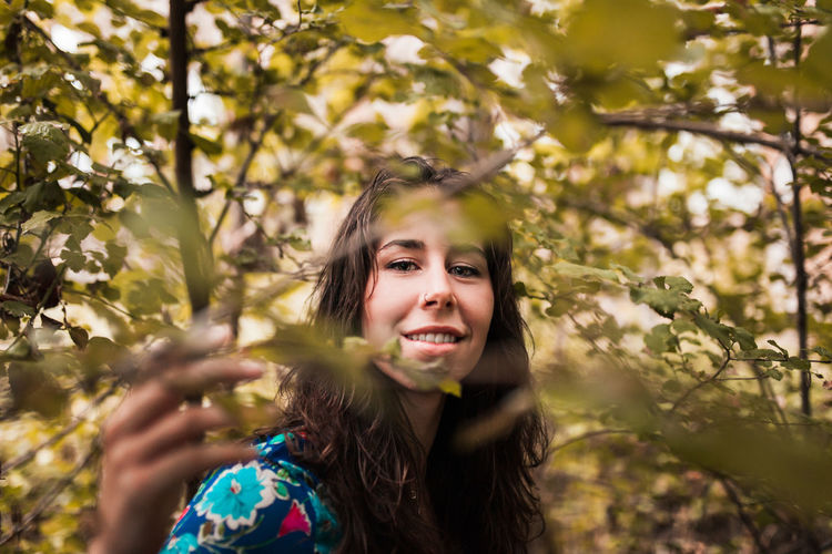 Portrait of smiling woman amidst trees