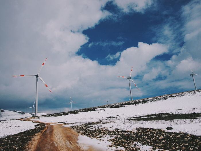 Low angle view of wind turbines on field against sky during winter