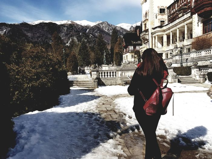 Architecture Beauty In Nature Building Exterior Built Structure Cold Temperature Day Full Length Leisure Activity Lifestyles Mountain Nature One Person Outdoors Real People Rear View Sky Snow Standing Sunlight Travel Destinations Tree Warm Clothing Winter Women Young Women