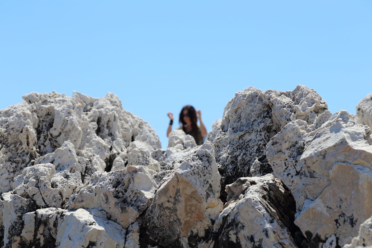 Rock formation by woman against clear blue sky