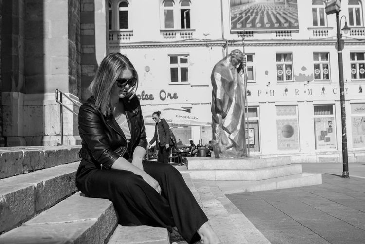 Woman sitting by statue in city