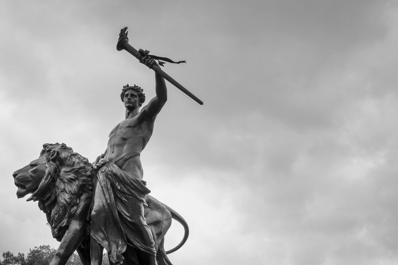 Progress, one of four bronze statues around the Victoria memorial monument in London. Black and white Art Black And White Britain Buckingham Palace Culture Historic Landmark Lion Man Monument Overcast Sky Progress Queen Royal Sculpture Sight Seeing Sightseeing Statue Throne Torch Tourist Attraction  Travel Destinations Uk Victoria Memorial Warrior