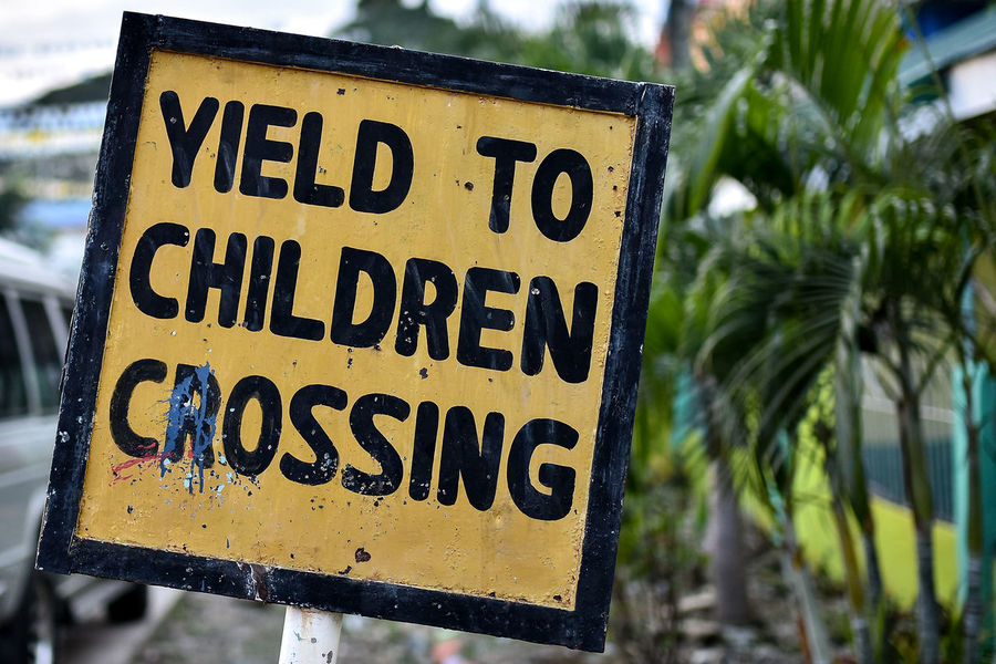 A hand made wonky 'Yield to Children' sign in yellow and black. Children Close-up Communication Day Focus On Foreground Hand Painted Hand Painted Sign No People Outdoors Safety Safety Sign Text Warning Sign Western Script Yeild Yellow Yield