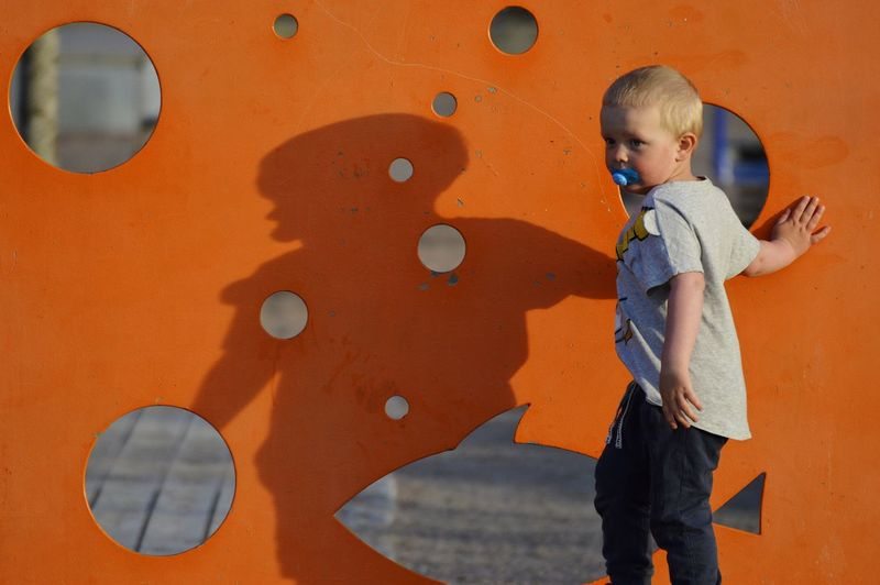 Cute boy looking away while standing by orange wall