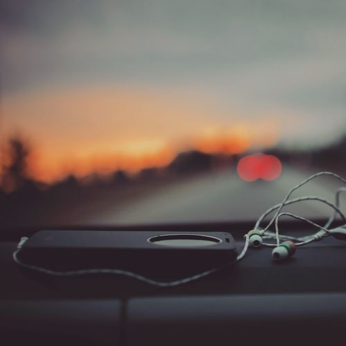 Close-up of mobile phone with in-ear headphones on car dashboard