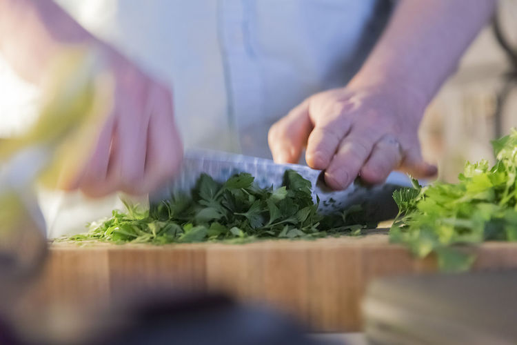 Close up view of a home chef chopping herbs on a wooden cutting board, motion blur. Authentic Moments Basel Cooking Hands Herbs Home Knife Low Light Man Married Authentic Chef Close Up Cutting Board Fingers Food Greens Kitchen Motion Organic Parsley Premium Collection Preparation  Skills  Wedding Ring
