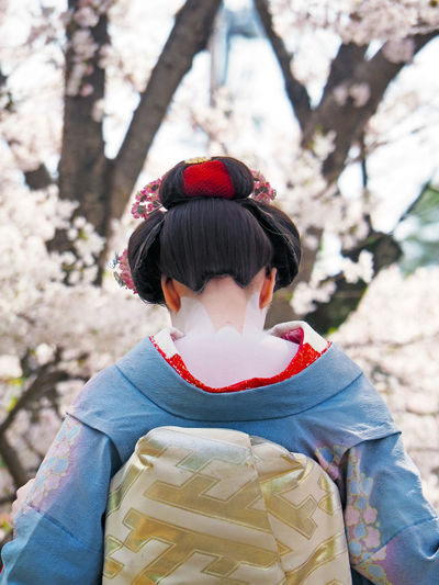 Rear View Of Woman Wearing Kimono Against Cherry Tree