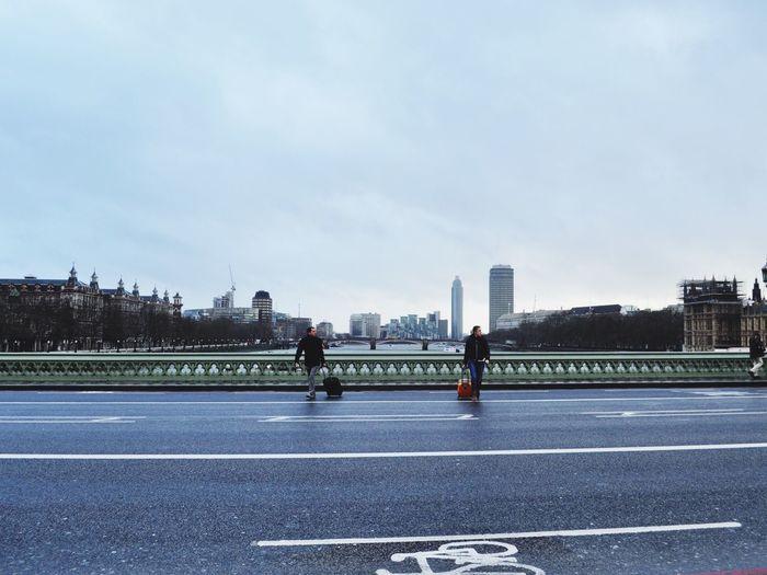 Man and woman with luggage walking on bridge