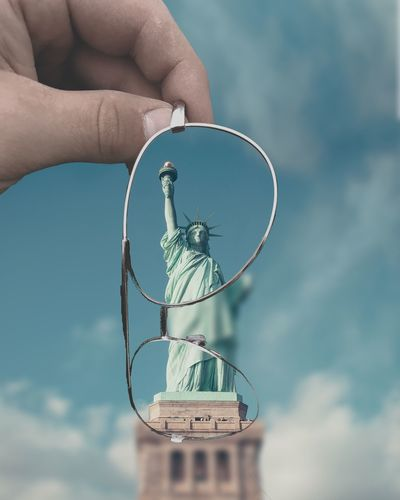 Cropped hand holding eyeglasses against statue of liberty