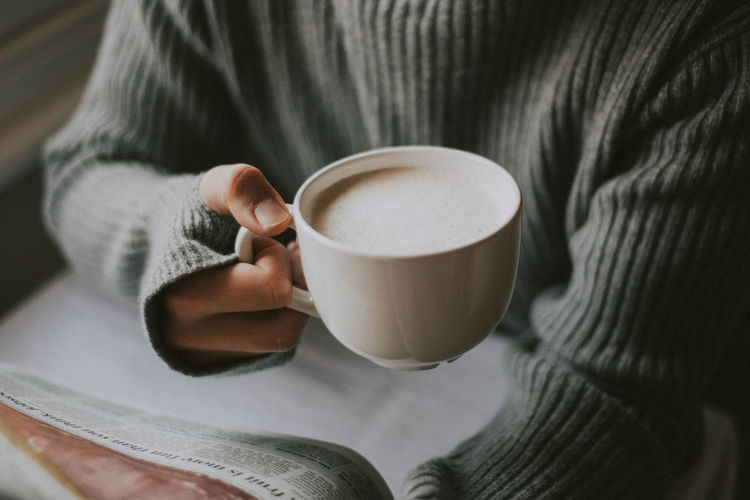 Midsection of person reading newspaper while holding coffee cup on table